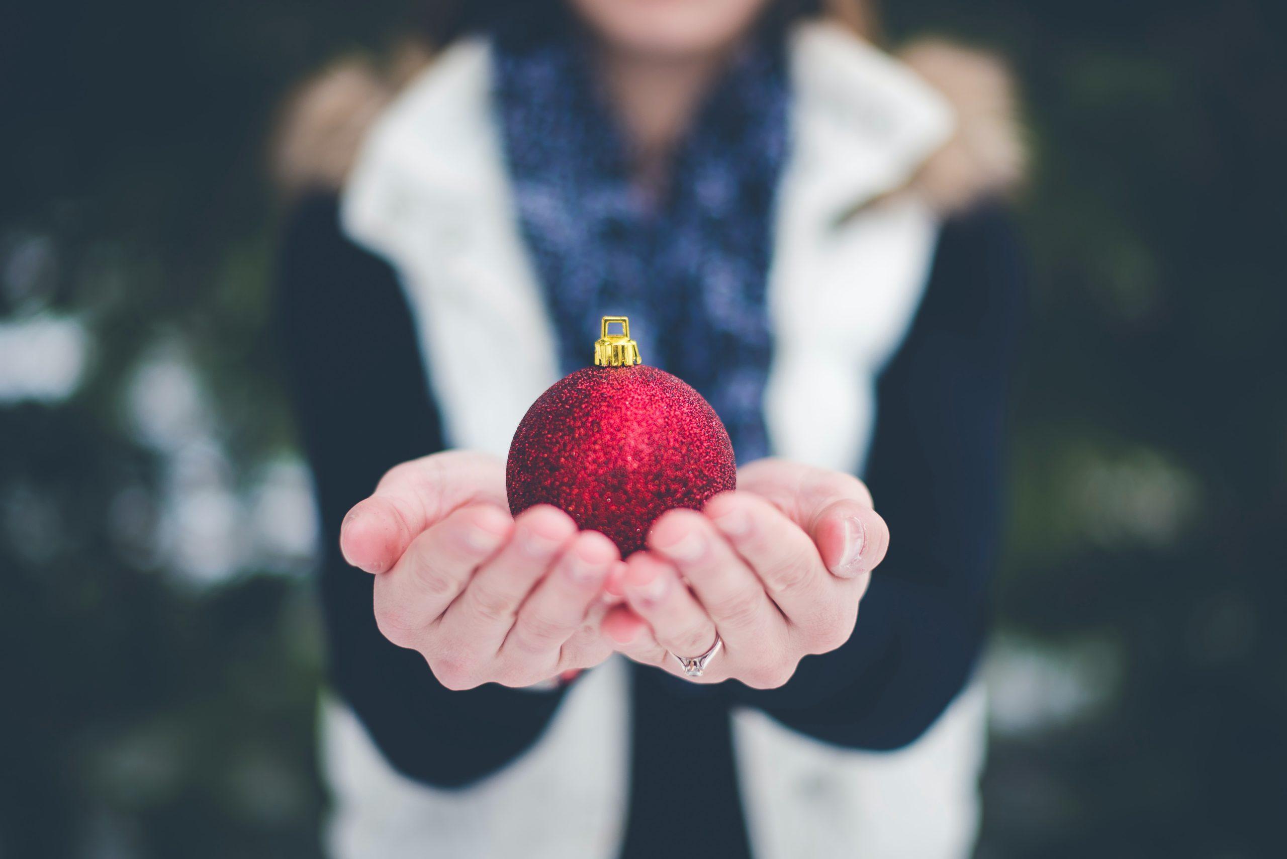 jul händer som håller en julgranskula med ring på finger